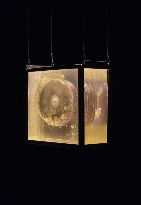Clear box with CD's encased in resin inside on black background