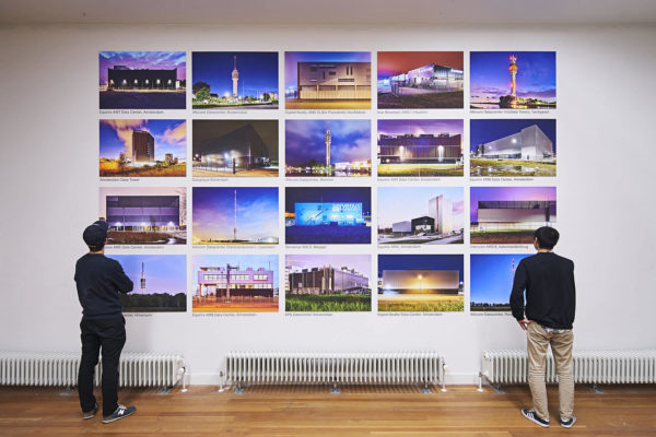 Two people looking at a grid of photographs of data centres mounted on a wall