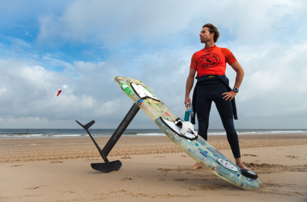 The Plastic Soup Surfer, Merijn Tinga, with his kitesurfing board made from plastic waste collected on the beach