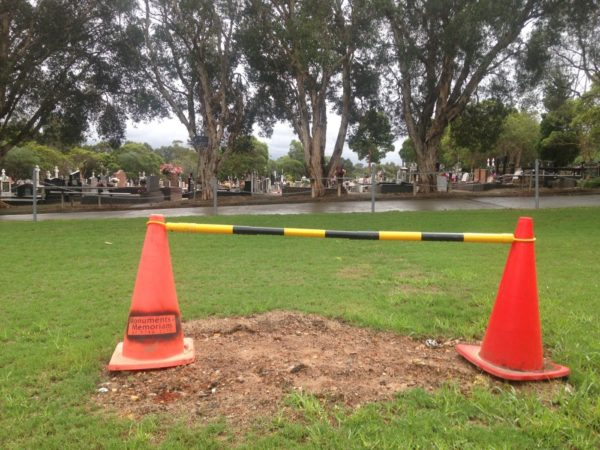 Two orange traffic cones with a yellow and black striped rod suspended between them on a lawn covering a patch of dirt