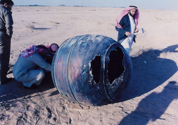 Curious onlookers examining a piece of space junk that landed in Saudi Arabia in 2001
